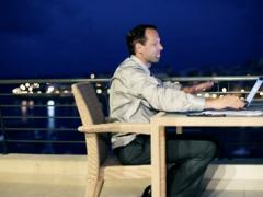 Frustrated businessman during work on the terrace in the evening, crane shot Stock Footage