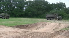 German soldiers advance past abandoned US Military vehicles Stock Footage