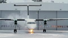 Small commuter passenger airplane taxing to defrost area - stock footage