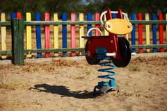 playground's wooden horse and moto - stock photo