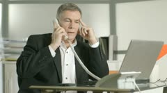 Businessman taking care of two phone calls Stock Footage