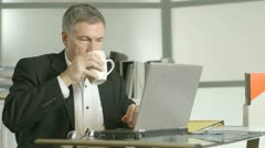 businessman with wrist pain at his desk - stock footage