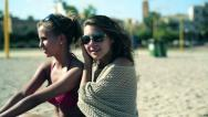Two female friends sitting on the beach and talking Stock Footage