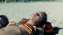 Sexy women lying on the beach and sunbathing Stock Footage
