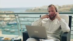 Happy man sitting on the terrace with laptop computer and cellphone Stock Footage