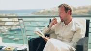Stock Video Footage of Young man sitting on the terrace reading book