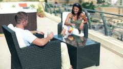 Happy couple with exotic drinks relaxing on the terrace, crane shot Stock Footage
