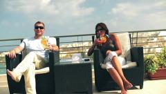 Happy couple with exotic drinks celebrating on the terrace, crane shot Stock Footage