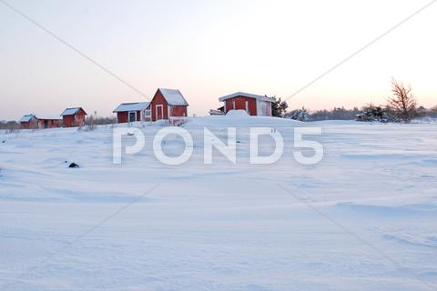 Stock photo of red cabins in winter dawn