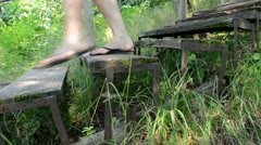 Woman in flip-flop shoes climb down retro wooden stairs in park Stock Footage