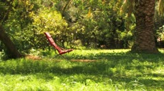 Red vintage chair at a large garden in summer Stock Footage