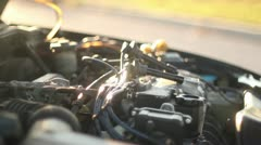 Man working on car installing spark plugs cu at sunset Stock Footage