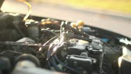 Stock Video Footage of man working on car installing spark plugs cu at sunset