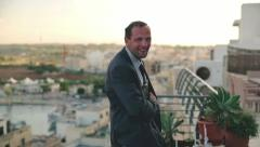 Portrait of businessman with tablet computer standing on the terrace, crane shot Stock Footage