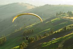 Paragliders Over Farmed Land In Beautiful Sunset Light Seen From Air - stock photo