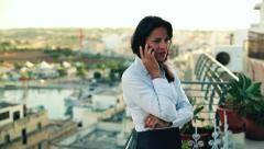 Young businesswoman talking on the cellphone on the terrace, crane shot Stock Footage