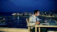 Businessman using laptop and tablet on the terrace in the evening, crane shot Stock Footage