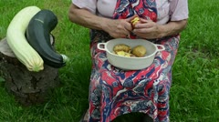 Old woman apron peeling shaving potato knife courgette stump Stock Footage