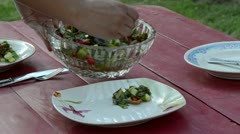 Hand put tomato cucumber onion salad in dish on outdoor table Stock Footage
