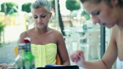 Female friends reading menu in the restaurant, steadicam shot - stock footage