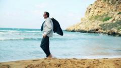 Stock Video Footage of Happy businessman walking on the beach and undress himself