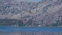 Canadair plane loading water from the lake Stock Footage