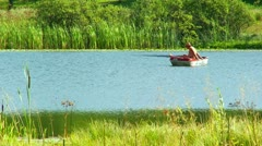 Fisherman in the boat enjoying on the sun and fishing at the lake Stock Footage