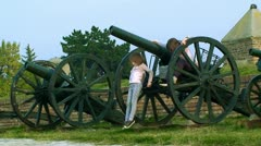 Girls playing in the exhibits of old military guns - stock footage
