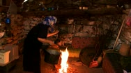 Old woman puts a pot on the fire for cooking in the stone hut in the village Stock Footage