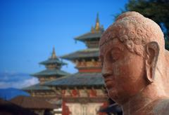 head of buddha, with pagoda in the background.. - stock photo