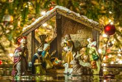 old handmade nativity scene in front of a christmas tree - stock photo