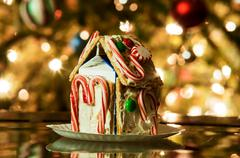 gingerbread house against a background of christmas tree lights - stock photo
