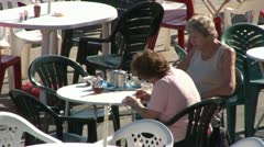 Two Old Women on Cafe Patio Stock Footage