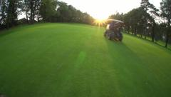 Golf Cart rides on fairway into sunset Stock Footage