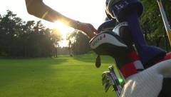 golfer takes golf club out of bag - stock footage