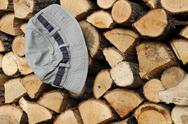 Stock Photo of stack of firewood and hat