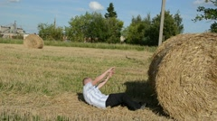 Man run strike hit fall down round straw bale agriculture field Stock Footage