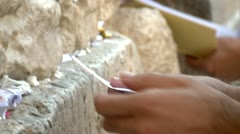 Folding and Putting a Note with Pray at the Western Wall 1 Stock Footage