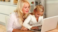 Mother and daughter using laptop at kitchen table Stock Footage