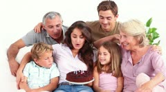 Family blowing candles on chocolate cake Stock Footage