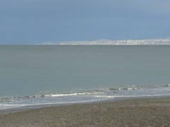 Volcanic beach at Hawke bay + Cape kidnappers in the distance Stock Footage