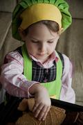 Child chef preparing and eating dessert Stock Photos
