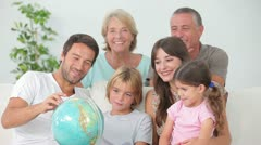 Multi-generation family all looking at globe - stock footage