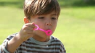 Little boy has fun blowing bubbles Stock Footage