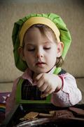 child chef preparing and eating dessert - stock photo