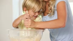 Mother and son mixing pastry in a bowl Stock Footage