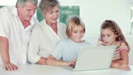 Siblings and grandparents using laptop Stock Footage