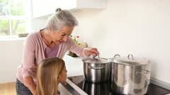 Girl happily cooking with her grandmother - stock footage