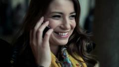 Beautiful woman talking on cellphone in city, steadicam shot HD - stock footage