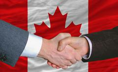 Businessmen handshake after good deal in front of canada flag Stock Photos